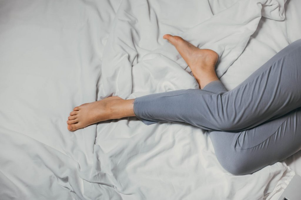anonymous woman lying on bed at home